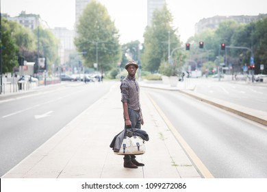 young handsome millennial black man outdoor posing looking away holding  duffle bag - customer, attitude concept