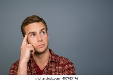 Young handsome minded man trying to find way to solve problem