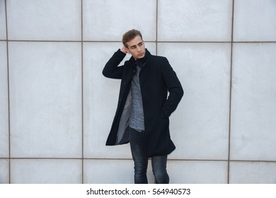 Young handsome modern blond businessman with blue eyes posing leaning against a white wall, looking in camera, wearing a coat - business, modern, hipster, success concept