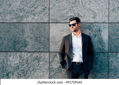 Young handsome modern businessman posing leaning against a wall, looking in camera, wearing a coat - business, success concept