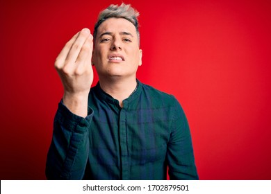 Young handsome modern man wearing elegant green shirt over red isolated background Doing Italian gesture with hand and fingers confident expression