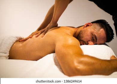 Young handsome muscle man laying down on the massage bed and male therapist giving him aroma oil remedial massage.