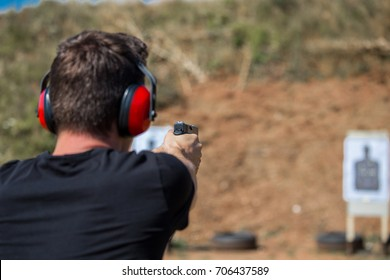Young and handsome muscular caucasian policeman professional army special force training on the battleground with firearms gun glock pistol firing at the enemy target stopping violent criminals