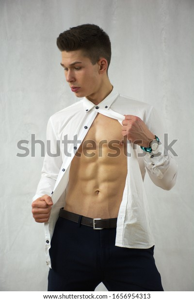 Young handsome muscular male model wearing white shirt showing perfect abs.