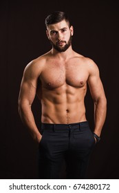 Young handsome muscular man with a beard, posing on a black back