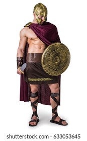Young handsome muscular man posing in roman or spartan gladiator costume with shield and sword, standing isolated on white background in studio
