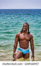 Young, handsome, muscular, shirtless African American man standing in the water and smiling, on Yelapa beach near Puerto Vallarta, Mexico.