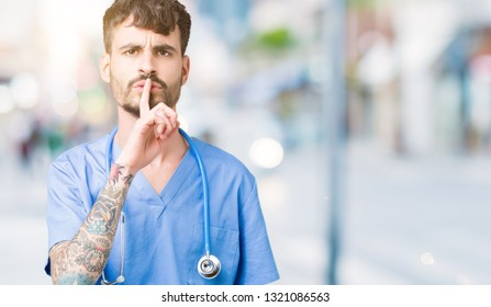 Young handsome nurse man wearing surgeon uniform over isolated background asking to be quiet with finger on lips. Silence and secret concept.