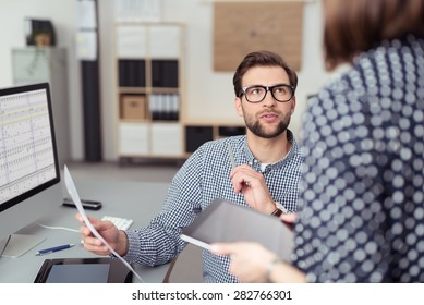 Young Handsome Office Man Talking to his Female Manager While Holding a Paper at his Working Table with Computer.