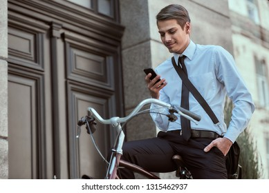 Young handsome office worker going to work on his bicycle. Healthy lifestyle concept.