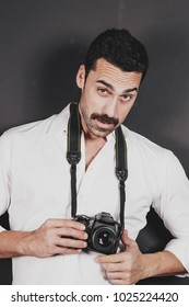 Young handsome photographer with beard and mustache holding a dslr camera, studio portrait