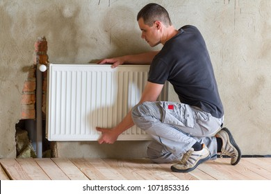 Young handsome professional plumber worker installing heating radiator in an empty room of a newly built apartment or house. Construction, maintenance and repair concept.