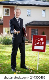 Young handsome real estate agent holding the keys to house for sale