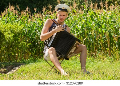 Young handsome sailor in frock and peaked cap playing the accordion on thickets of corn background.