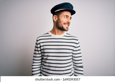 Young handsome sailor man with beard wearing navy striped uniform and captain hat looking away to side with smile on face, natural expression. Laughing confident.