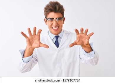 Young handsome sciencist man wearing glasses and coat over isolated white background smiling funny doing claw gesture as cat, aggressive and sexy expression