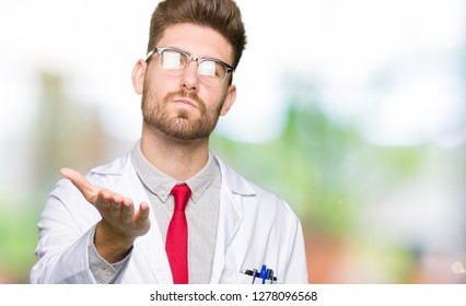 Young handsome scientist man wearing glasses looking at the camera blowing a kiss with hand on air being lovely and sexy. Love expression.