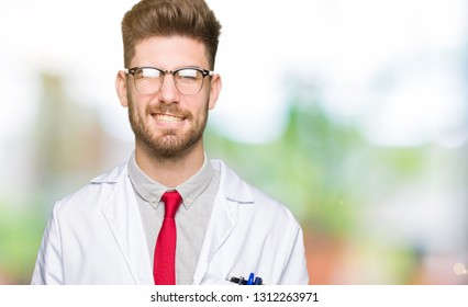 Young handsome scientist man wearing glasses winking looking at the camera with sexy expression, cheerful and happy face.
