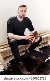 Young handsome serious man in total black outfit and brown leather boots sits on wooden bench, holds vintage american soccer ball and looks in camera, isolated on white background