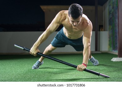 Young handsome shirtless man doing push ups with barbell bar in the outdoor gym at night.