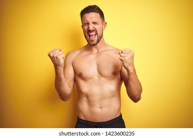 Young handsome shirtless man over isolated yellow background very happy and excited doing winner gesture with arms raised, smiling and screaming for success. Celebration concept.