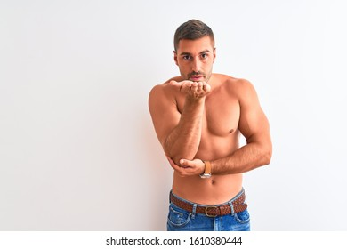 Young handsome shirtless man showing muscular body over isolated background looking at the camera blowing a kiss with hand on air being lovely and sexy. Love expression.