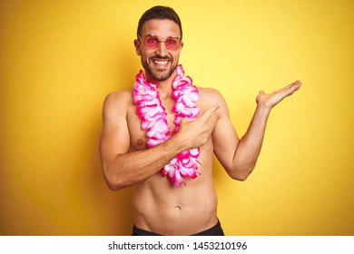 Young handsome shirtless man wearing sunglasses and pink hawaiian lei over yellow background amazed and smiling to the camera while presenting with hand and pointing with finger.