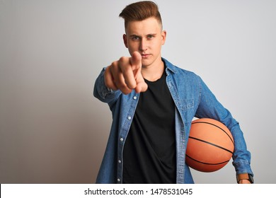 Young handsome shopkeeper man holding folded jeans over isolated white background pointing with finger to the camera and to you, hand sign, positive and confident gesture from the front