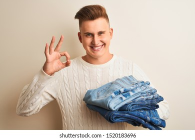 Young handsome shopkeeper man holding folded jeans over isolated white background doing ok sign with fingers, excellent symbol