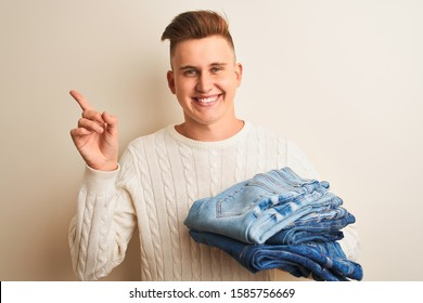 Young handsome shopkeeper man holding folded jeans over isolated white background very happy pointing with hand and finger to the side