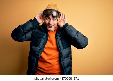 Young handsome skier man skiing wearing snow sportswear using ski goggles Smiling pulling ears with fingers, funny gesture. Audition problem