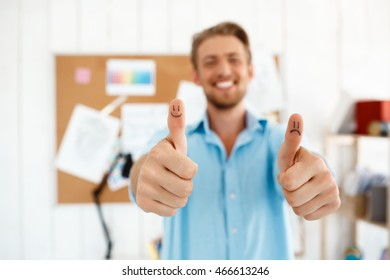Young handsome smiling businessman showing thumbs up with funny faces drawings. Focus on hands. White modern office interior background.