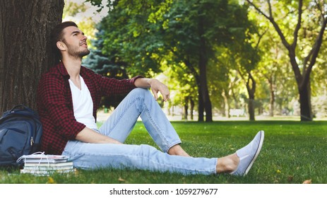 Young handsome smiling man sitting on the grass, having a rest with books nearby looking up