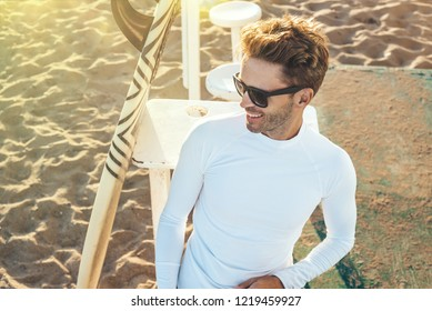 Young handsome smiling man is sitting on a beach next to his surfboard wearing dark sunglasses and white blank long-sleeve lycra shirt. Vertical mock-up style.