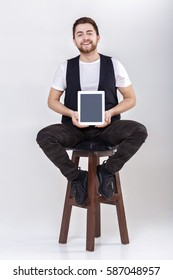 young handsome smilling man with beard in white shirt and black waistcoat holding tablet and sits on chair on gray background