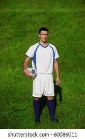 Young handsome soccer player on green grass