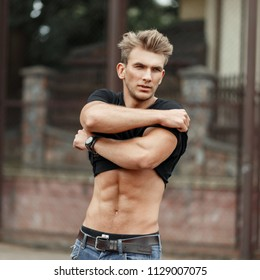 Young handsome sport model man with a healthy body takes off his shirt on the street