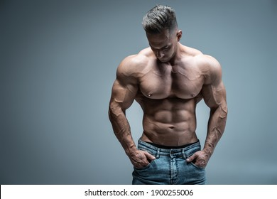 young handsome sportsman bodybuilder posing in jeans on grey background