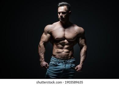 young handsome sportsman bodybuilder posing in jeans on black background