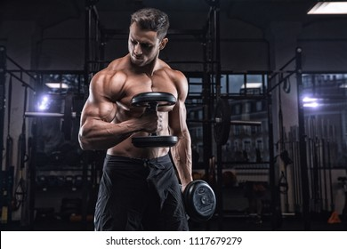 Young handsome sportsman bodybuilder weightlifter with an ideal body, after coaching poses in front of the camera, abdominal muscles, biceps triceps. In sportswear.