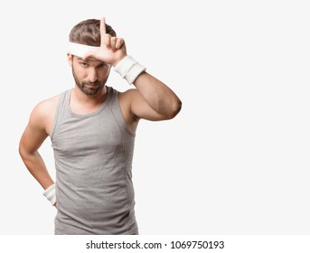 young handsome sportsman loser sign wearing gray tank top . person isolated against monochrome background