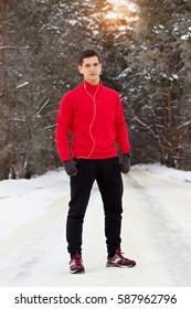 Young and handsome sportsman in red sweater  standing in the park and listening music. Outdoor activity.