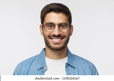 Young handsome student isolated on gray background, in blue shirt, wearing trendy round glasses, looking at camera with happy smile