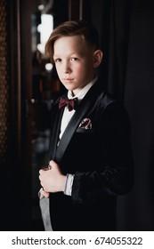 Young handsome stylish boy posing in velvet jacket