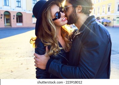 Young handsome stylish guy listing her pretty blonde girlfriend, romantic sensual couple hugs on the street of european city at bright evening sunlight, rock n roll styled clothes and sunglasses.