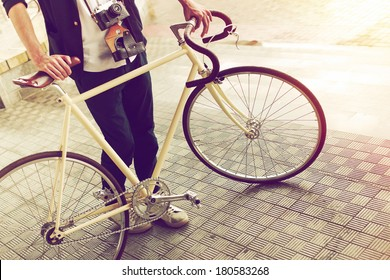 Young handsome stylish hipster man posing on the street with vintage camera and bike on the street in sunny summer day