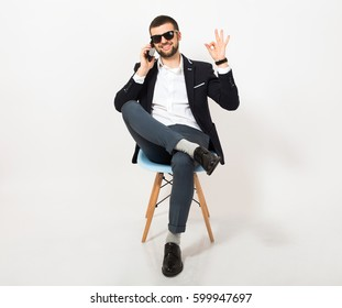 young handsome stylish hipster man in black jacket, business style, white shirt, isolated, sitting relaxed on office chair, talking on smartphone, smiling, happy, positive, sunglasses, ok sign