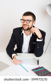 young handsome stylish hipster man in black jacket working at office table, business style, white shirt, isolated, laptop, start up, work place, thinking, documents, glasses, smiling, happy, positive