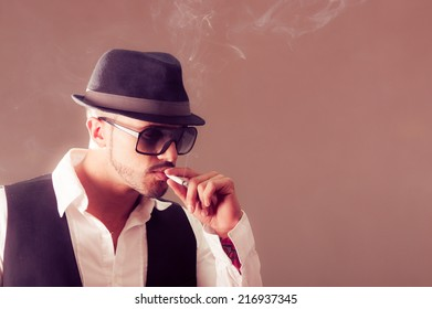 Young handsome stylish male model wearing a hat smoking a cigarette
