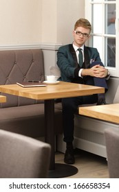 Young handsome stylish man fashion model relaxing thinking and waiting in cafe /restaurant with coffee